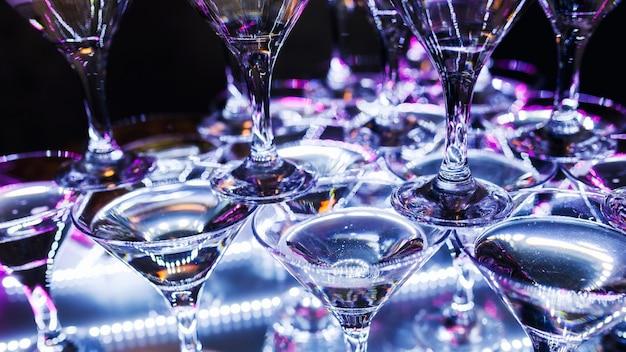 Piramide di champagne. alcool multicolore a una festa. bicchieri da vino in luce al neon. sfondo. focus spostato ubriachezza collettiva.