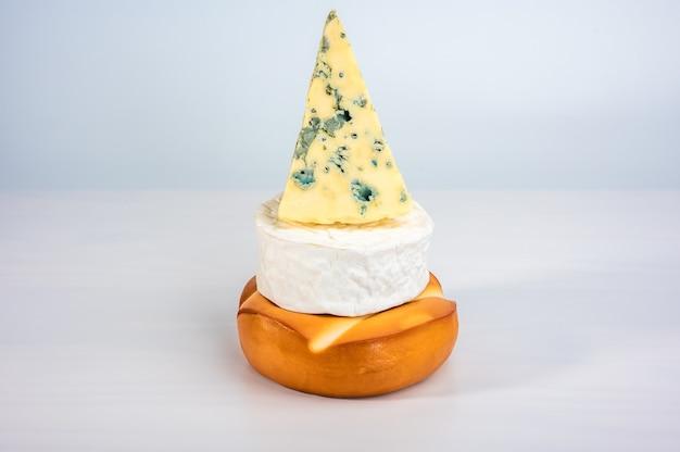 Piramide di formaggio. formaggio affumicato, brie e formaggio ammuffito sono impilati uno sopra l'altro. pila di selezione di formaggi
