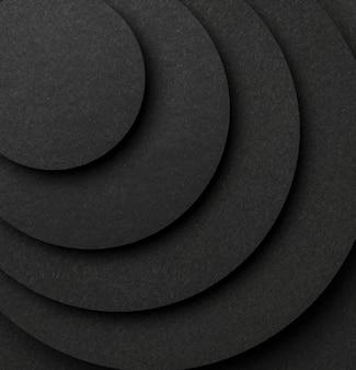 Piramide di pezzi circolari di carta nera close-up Foto Premium