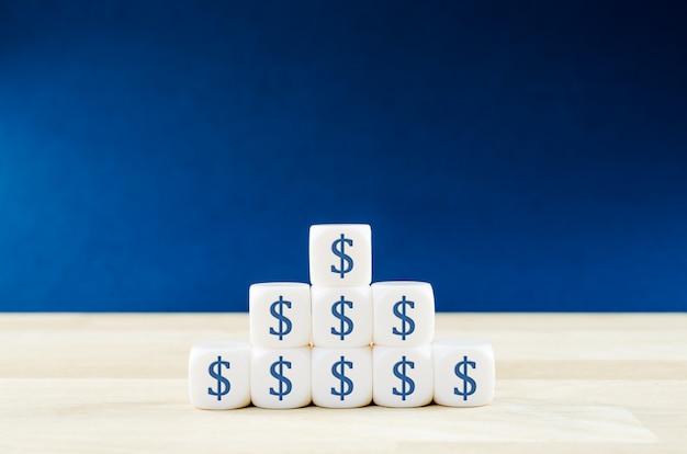 Fondamenta a forma di piramide di fogli bianchi di post-it con il simbolo del dollaro su di essi in un'immagine concettuale di profitto e potere.