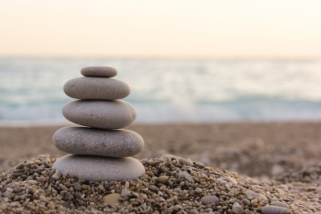 Piramide di pietre zen lisce sulla spiaggia.