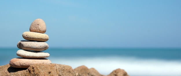 Piramide di pietre sulla riva del mare blu, armonia, panoramica