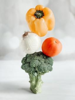 Una piramide di verdure, broccoli, pomodoro, cipolla, pepe su uno sfondo chiaro. levitazione di verdure, verdure fumanti, concetto di cibo sano.