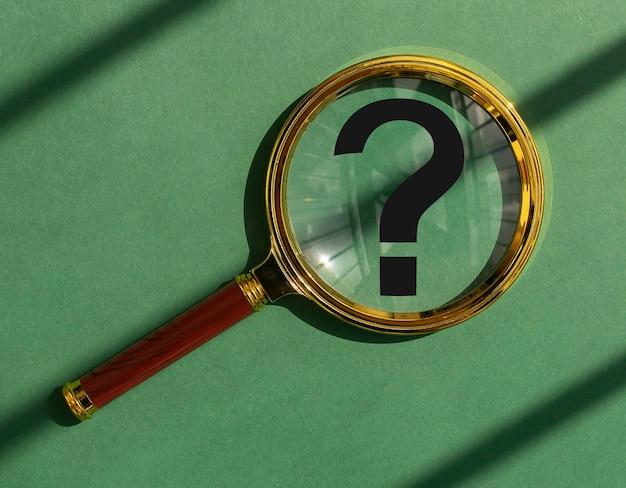 Q concetto punto interrogativo o segno nella lente della lente d'ingrandimento lente d'ingrandimento su sfondo verde