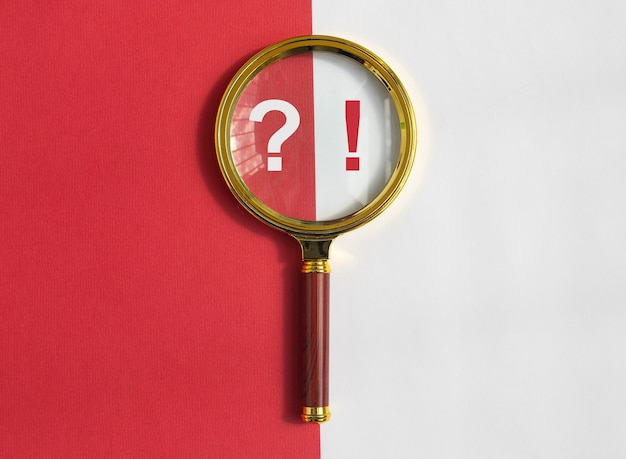 Qa concept lente d'ingrandimento dorata con punti interrogativi ed esclamativi su sfondo rosso e bianco