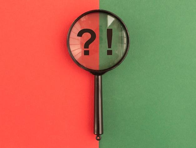 Lente d'ingrandimento del concetto qna con punti interrogativi ed esclamativi su sfondo rosso e verde