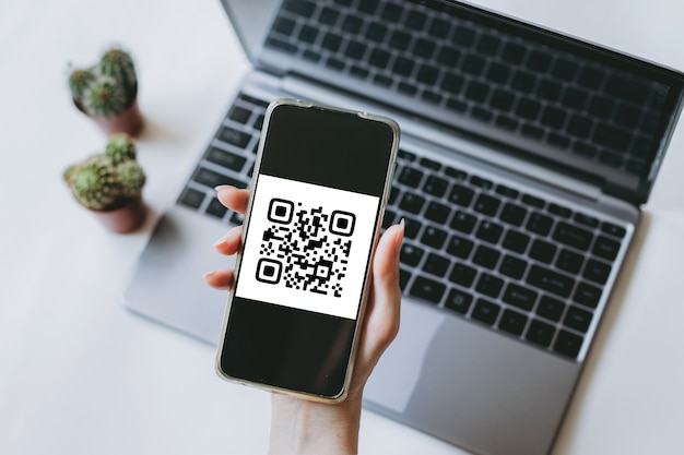 Scansione del codice qr pagamento e concetto di tecnologia senza contanti la mano femminile utilizza un telefono cellulare