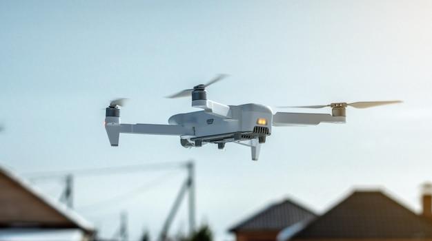 Un drone quadricottero con telecamera è sospeso in aria contro un cielo blu
