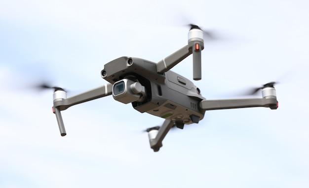 Mosca di quadrocopter nel fondo del primo piano del cielo