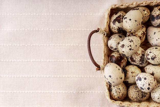 Uovo di quaglia nel cestino sulla trama del tessuto.