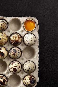Uova di quaglia nell'imballaggio di cartone sul tavolo grigio graffiato.