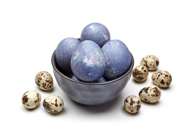 Uova di quaglia e uova di gallina colorate in una ciotola su un bianco. concetto di pasqua