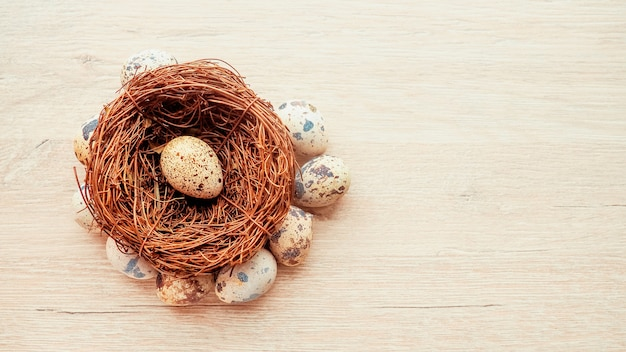 Uova di quaglia in un nido di rami sdraiati su uno sfondo di legno, una cartolina per pasqua.