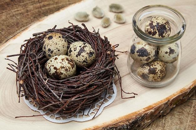 Uova di quaglia in un nido fatto di rami e un barattolo di vetro con uova su un supporto di legno naturale