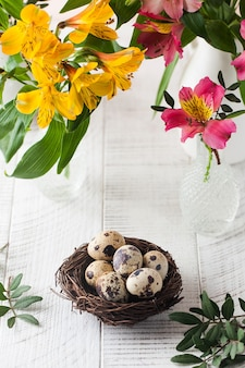Uova di quaglia in un nido con fiori gialli e rosa su fondo di legno bianco.