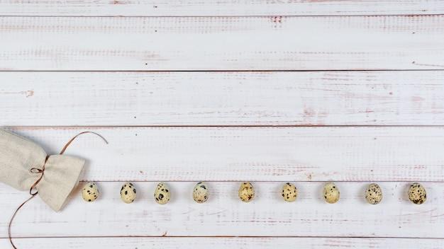 Le uova di quaglia rotolano fuori da un sacchetto di tela su fondo di legno piatto vista dall'alto