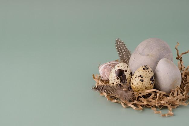 Uova di quaglia, pietre rotonde e piume giacciono su uno sfondo blu pastello, primo piano. fondo moderno naturale di pasqua. concetto di pasqua minimalista creativo.