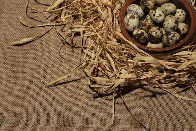 Uova di quaglia su un piatto di legno sopra fondo di legno vecchio scuro.