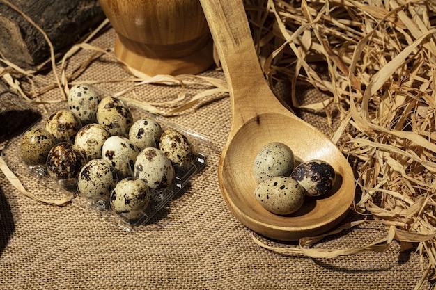 Uova di quaglia su un cucchiaio di legno sopra fondo di legno vecchio scuro.