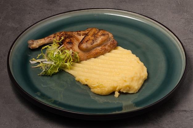 Quaglia con purè di patate su un piatto verde su sfondo grigio