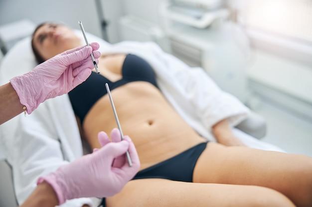 Dermatologo femminile qualificato in guanti di lattice che tiene in mano uno strumento per biopsia in acciaio inossidabile