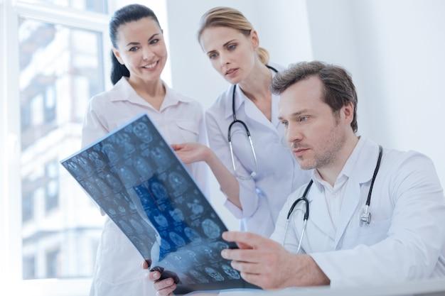 Neurologo attento maturo qualificato che lavora e analizza l'immagine a raggi x del cervello in laboratorio mentre i colleghi condividono opinioni