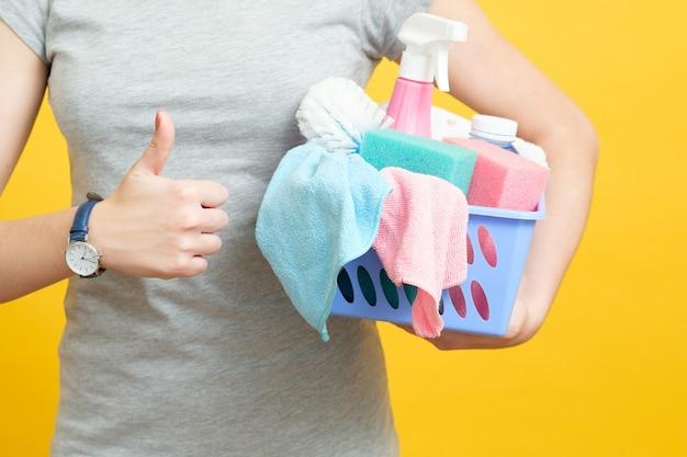 Pulizia di qualità. casalinga pollice in su. donna con cesto di prodotti per la pulizia su giallo.