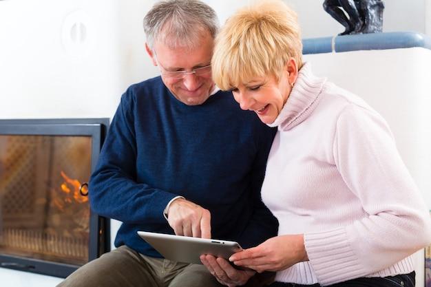 Qualità della vita: due persone anziane sedute a casa davanti alla fornace, scrivendo e-mail sul tablet