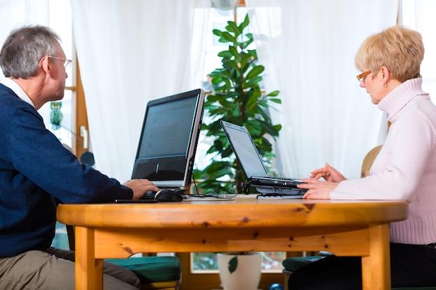 Qualità della vita: due anziani seduti a casa sul tavolo e scrivono e-mail sul computer e sul laptop