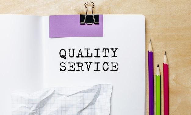 Testo di servizio di qualità scritto su una carta con le matite sulla scrivania in ufficio