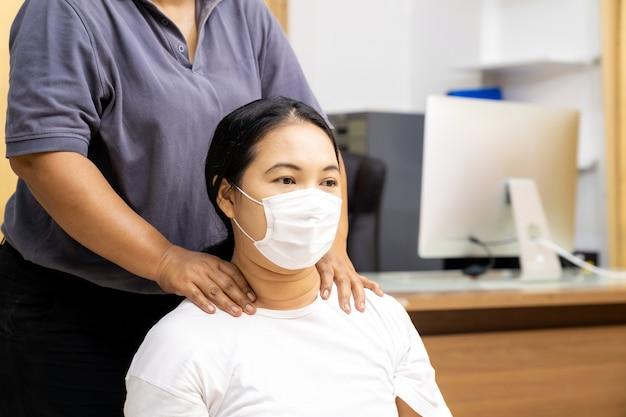 La donna asiatica in quarantena fa il massaggio a casa con la maschera