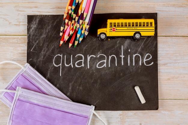 Quarantena a scuola per il concetto di studente. lavagna, matite e bus giocattolo.