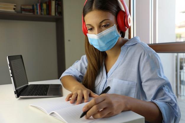 Quarantena giovane donna che studia da casa per la malattia virale 2019-ncov. concetto di scuola intelligente.