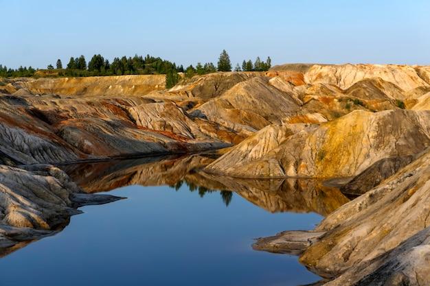 Cava di estrazione di caolino con bei pendii multicolori e un lago in primo piano