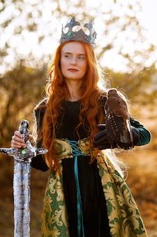 Regina con i capelli rossi in un abito verde con una corona e una spada vicino a un cavallo con un uccello