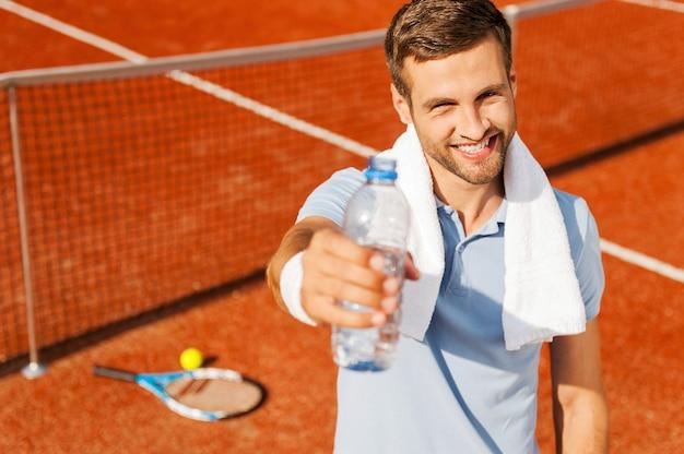 Placa la tua sete! felice giovane uomo in polo e asciugamano sulle spalle allungando la bottiglia con acqua mentre si sta in piedi sul campo da tennis