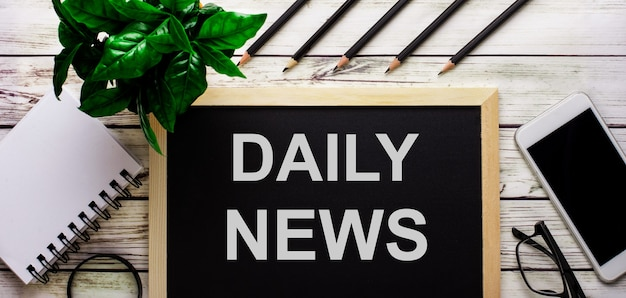 Domanda daily news è scritta in bianco su una lavagna nera accanto a un telefono, un blocco note, occhiali, matite e una pianta verde.