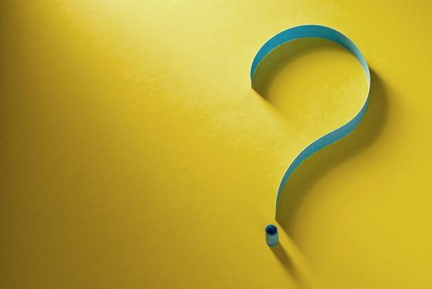 Punto interrogativo di carta blu arrotolata su sfondo giallo colorato