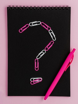 Punto interrogativo fatto di clip sul taccuino nero in bianco su sfondo rosa.