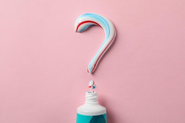 Punto interrogativo fatto di dentifricio e tubo sulla superficie rosa