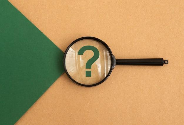 Punto interrogativo attraverso la lente di ingrandimento su sfondo verde e marrone vista dall'alto concetto di que...