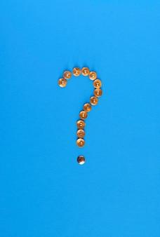 Un punto interrogativo è stato fatto da puntine da disegno su una superficie blu.