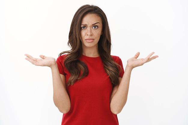 La donna bruna delusa e interrogata in maglietta rossa alza il sopracciglio scettica e sospettosa, alza le spalle con le mani in alto, fa una smorfia dispiaciuta, vede una strana situazione senza senso