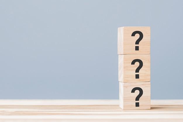 Punto interrogativo (?) sul blocco cubo di legno sullo sfondo della tabella. faq (domande frequenti), risposta, domande e risposte, informazioni, comunicazione e concetti di interrogazione