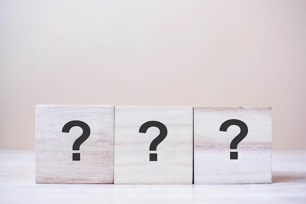 Punto interrogativo (?) sul cubo di legno sul tavolo di fondo.