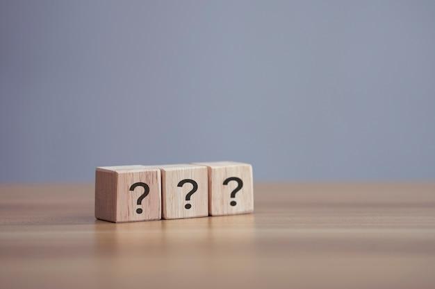 Domande segna la parola nel blocco cubo di legno sullo sfondo del tavolo