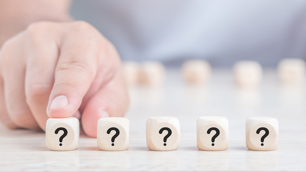 Domande segna le parole in blocchi di cubo di legno sullo sfondo del tavolo