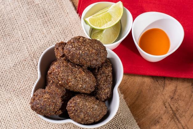 Quibe tipico spuntino brasiliano di carne su piatto bianco con limoni e salsa all'arancia su panni da cucina