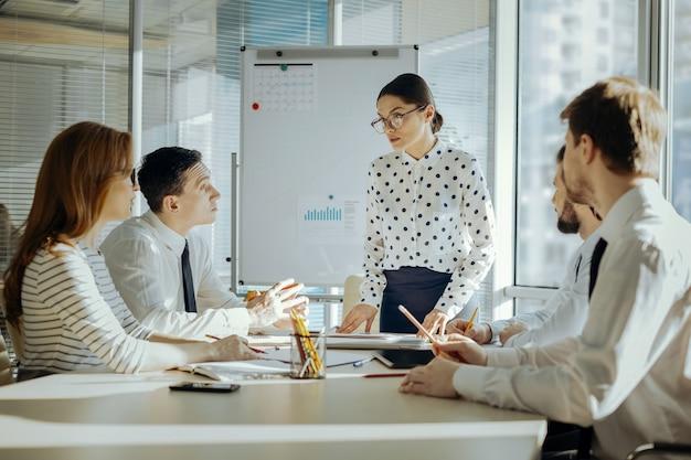 Istruzioni rapide. affascinante giovane capo femminile che risponde alle domande dei suoi colleghi relative a problemi di lavoro mentre ha un briefing mattutino con loro