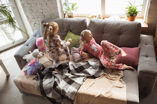 Bambine tranquille che giocano in una camera da letto in pigiama carino stile casa e comfort